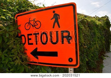 A detour sign leads bikers and pedestrians into the bushes