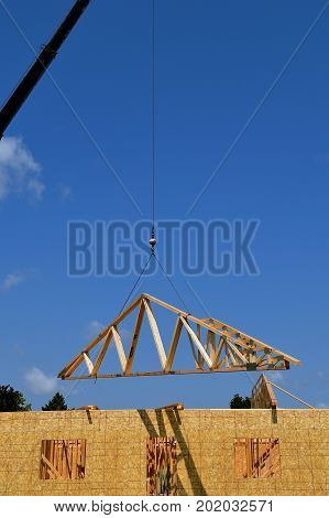 A boom and cable transfer a load of pre-made rafter to the top of a building under construction.
