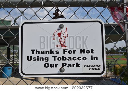 A sign attached to a fence educates the public the use of tobacco in a baseball park is prohibited.