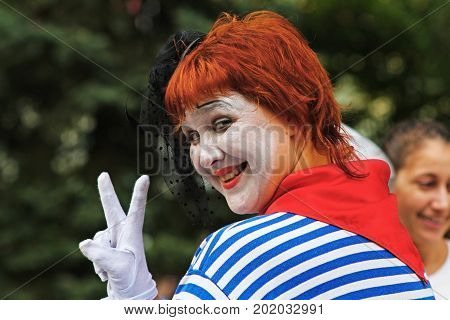 Volgograd Russia - September 01 2013: Portrait of smiling female street artist showing victory sign at the City Day in Volgograd