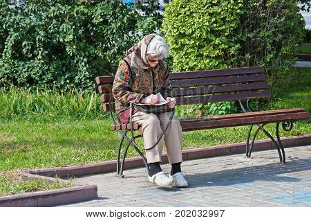 Volgograd Russia - September 11 2011: Old woman sits on the bench and unravels a crossword puzzle in the park in Volgograd
