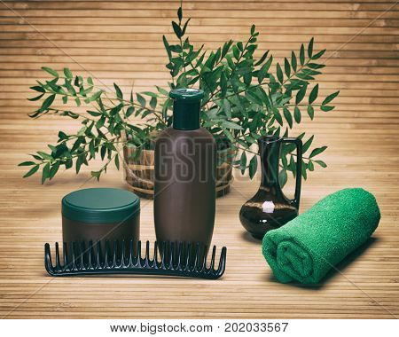Natural hair beauty products. Shampoo, hair mask, comb and towel with green plant branches in wooden basket. Toned image