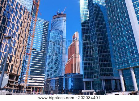 MOSCOW, APR, 28, 2015: Bottom view on business buildings offices of Moscow-City business center, construction cranes. Moscow financial business architecture. Famous Moscow sightseeing points tours
