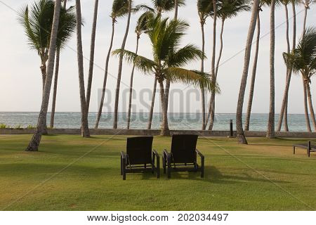 Vacation Time Background Of Two Beach Lounge Chairs Under Grass Tent On Beach