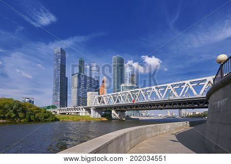 View on Moscow City business center skyscrapers office buildings, luxury apartments, metal railway bridge across river. Moscow city skyscrapers panorama. Modern european russian architecture cityscape