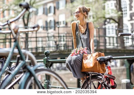 Young and beautiful woman sitting with bag and flowers near the water channel in Amsterdam old city