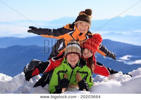 Happy young boys and girls on summit of snowy mountain in Winter.
