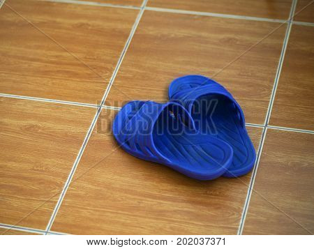 COLOR PHOTO OF CLOSEUP OF RUBBER SANDAL ON FLOOR