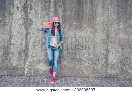 Cool Swag Culture. Young Attractive Hipster Girl Stands With Pink Skate Board On Concrete Wall`s Bac