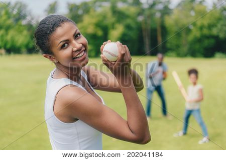 selective focus of smiling african american woman with baseball ball looking at camera