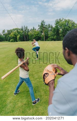 young african american family with one child playing baseball on green lawn