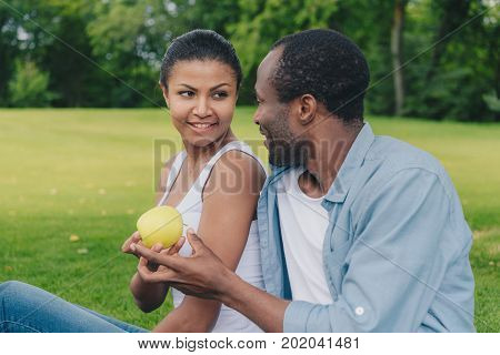 portrait of smiling african american woman giving fresh green apple to man