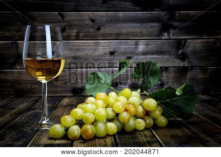 Wine Glass And Fresh Bunch Of White Grapes On Antique Wooden Background.