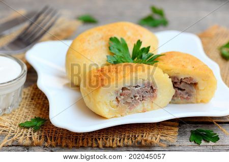Potato cutlets with mince meat filling on a white plate and a vintage wooden table. Boiled, mashed and seasoned potatoes filled with cooked mince meat filling. Closeup
