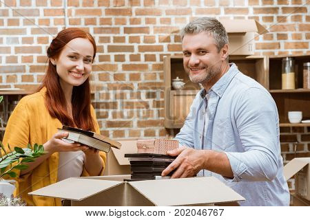 portrait of happy couple looking at camera while unpacking box at new home