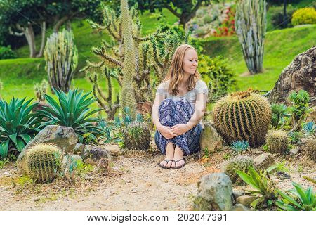 A Young Woman Sits On The Ground Among The Cactus. Spiny Concept. Out Of Comfort Zone Concept