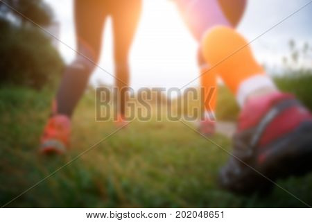 Blurred photo from below of two running women in forest, flare natural