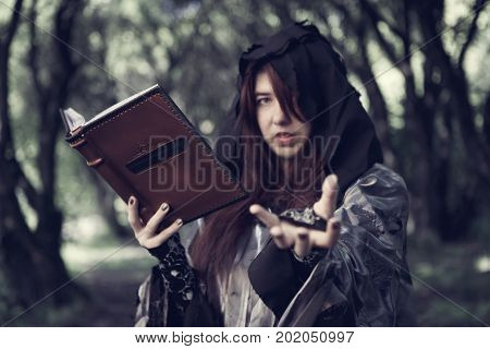 Toned photo of young witch with book of spells in forest
