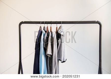 Close up mobile clothes rack with man's clothes hanging on it on white background