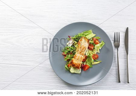 Delicious salmon with salad and flatware on wooden table