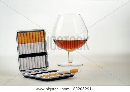 Tobacco and alcohol cigarette case with filter cigarettes and a glass with cognac or brandy on a light gray background with copy space health concept selected focus narrow depth of field