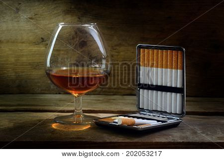 Alcohol and tobacco glass with cognac or brandy and a case with filter cigarettes on warm rustic wood concept for enjoyment or addiction selected focus narrow depth of field