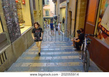 PALMA DE MALLORCA, SPAIN - AUGUST 18 2017: Unidentified people walking in an alley and enjoying the beautiful old streets of Palma de Mallorca, Spain.