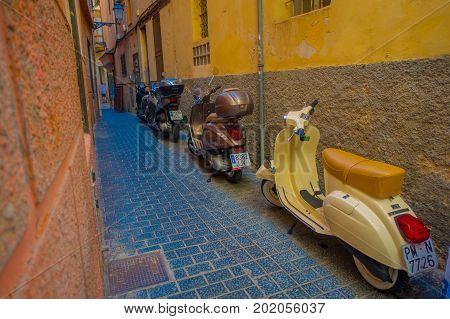 PALMA DE MALLORCA, SPAIN - AUGUST 18 2017: Motorcycles parked in an alley in Palma de Mallorca, Balearic islands, Spain.