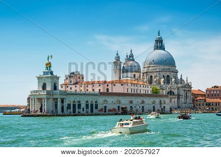 Venice, Italy - May 18, 2017: Water taxis are sailing along the Grand Canal in Venice. Motor boats are the main transport in Venice. Santa Maria della Salute church in the distance.