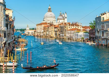 Venice, Italy - May 18, 2017: Gondola and water taxis are sailing along the Grand Canal. Grand Canal is one of the major water-traffic corridors in Venice. Santa Maria della Salute church in the distance.