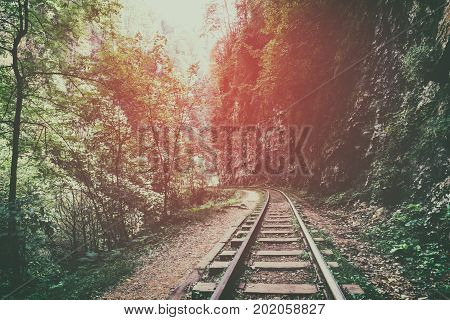 railway  or railroad among mountains, rocks and wild forests at sunset in the fog, dramatic mysterious landscape, toned