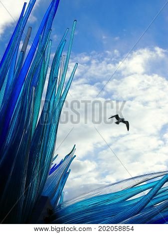 Blue glass sculpture in murano venice with bird flying in summer sky with white clouds