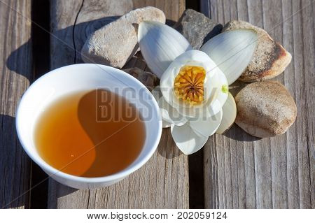 Cup of tea in the form of Yin Yang symbol with a water-lily on a wooden surface. Top view