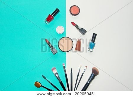 Cosmetics white and blue background with make up artist objects: lipstick eye shadows mascara eyeliner concealer nail polish. Lifestyle Concept
