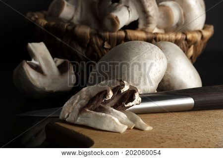 Mushrooms Champignons In A Wicker Basket With A Cutting Board And Knife