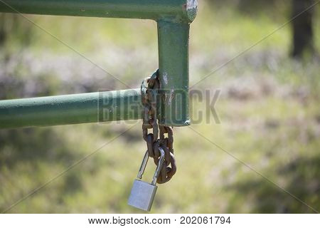 Open gate with a rusted chain and lock hanging from it