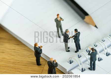 business agreement concept as miniature people businessmen handshaking and others clapping on notebook.