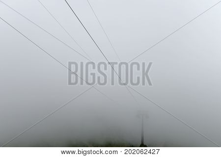 Mast cableway in the mountains enveloped in a thick fog