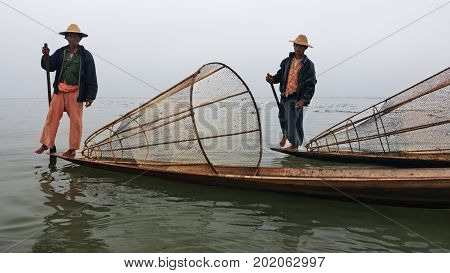 Inle Lake Myanmar - January 04 2007: Two local fishers with traditional Burmese fishing nets standing on stern of long boats and rowing oars by leg on Inle lake Shan state Myanmar.