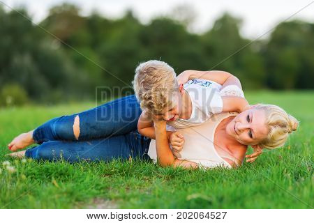 Woman Romps With Her Son On The Grass