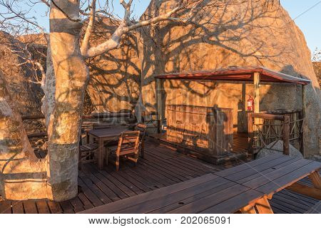 HOADA NAMIBIA - JUNE 27 2017: A bar between boulders on a hill at the Hoada Camp at sunset in the Kunene Region of Namibia