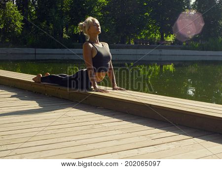 Young attractive woman doing yoga exercises in the park. Urdhva mukha svanasana