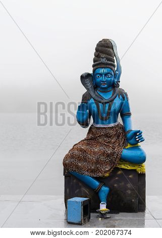 Statue of Shiva in a hindu temple (Grand Basin) in the day with fog mystical atmosphere.Mauritius