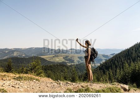 Young female backpacker uses mobile phone for self portrait in rural mountain area of ukrainian carpathian mountains. Girl with tourist rucksack on a long hiking walk looking for network connection