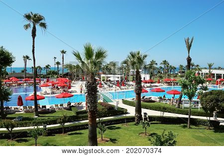 Belek, Turkey - June 01, 2015: View of territory with palm trees and red umbrellas near the beach in IC Hotel Santai Family Resort, Turkey.