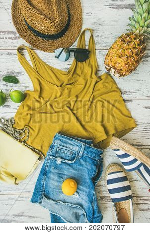 Colorful summer fashion outfit flat-lay. Denim shorts, straw sun hat, yellow top, espadrillas, yellow leather bag, sunglasses, pineapple, limes and lemon over pastel parquet background, top view