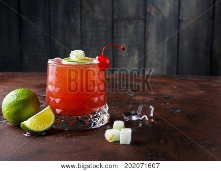 Red cocktail on wooden background. Refreshing alcohol drink with tequila, citrus juice, lime and maraschino cherry on brown marbled table with melting ice and dices of refined sugar, copy space