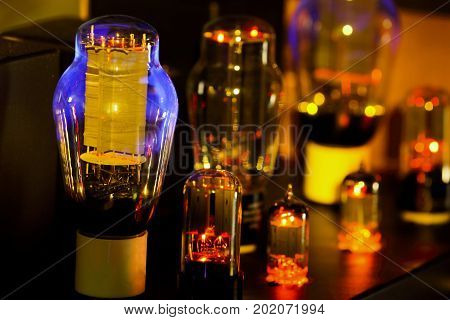 Night pictures of hi fi vacuum tubes amplifier Old-fashioned electronic device amplifier with glowing bulb diode lamp for sound reproduction . Focus only lamp