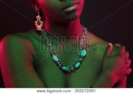 Colorful and creative portrait of an beautiful african womans bare upper body with necklace and jewelry. Dark skin with red and green light .