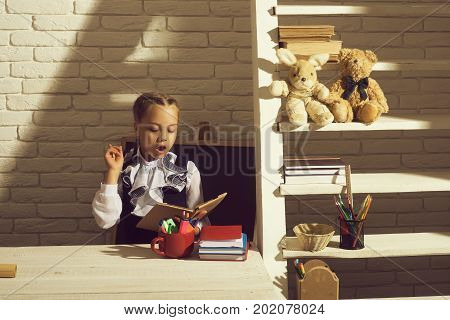 Schoolgirl With Busy Face Reads Book. Girl Sits At Desk